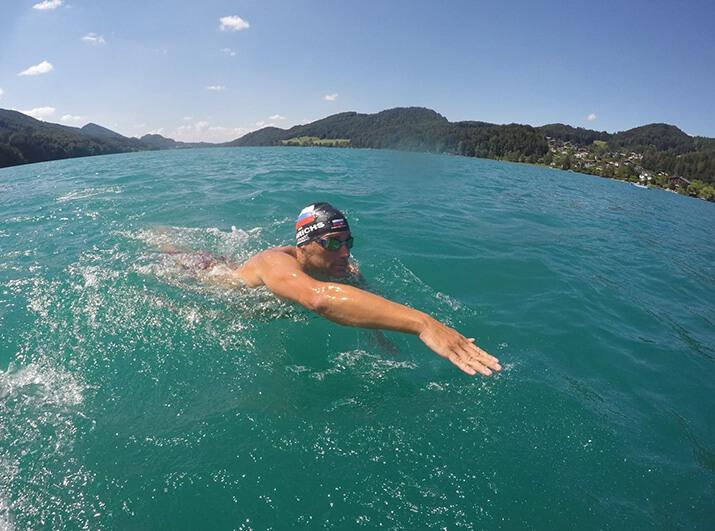 Schwimmexperte Marco Henrichs im Freiwasser mit Badekappe, macht einen Kraularmzug, hält den Kopf über Wasser