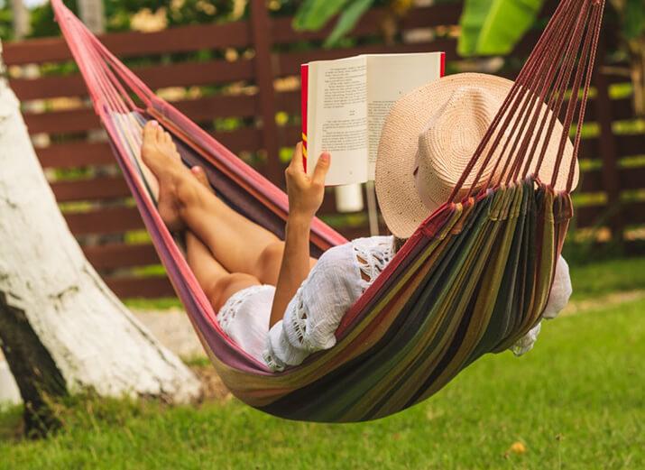 Eine Frau trägt einen Strohhut und liegt in einer Hängematte. Dabei liest sie ein Buch.