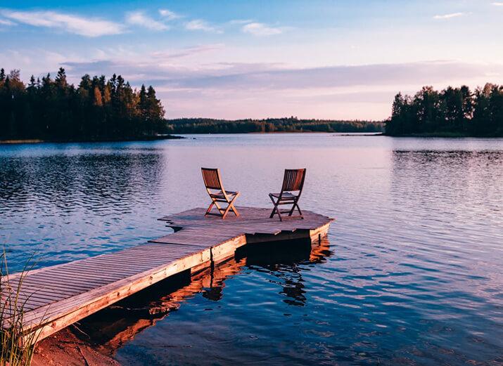 Zwei Stühle auf einem Steg an einem großen See bei Sonnenuntergang.