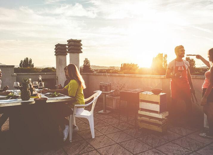 Mehrere Freunde sitzen auf einer Terrasse beisammen und veranstalten eine Grillparty.