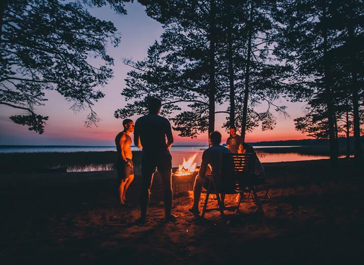 Mehrere Menschen sitzen bei Sonnenuntergang  um ein Lagerfeuer herum.