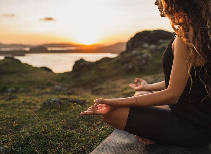 Eine Frau sitzt im Schneidersitz auf einer Matte und meditiert im Freien.