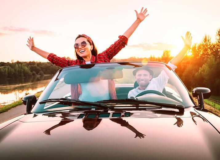 Zwei Freunde sitzen im Cabrio. Sie haben die Arme ausgestreckt und hören Musik.