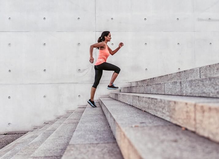 Eine Frau joggt eine Treppe hinauf