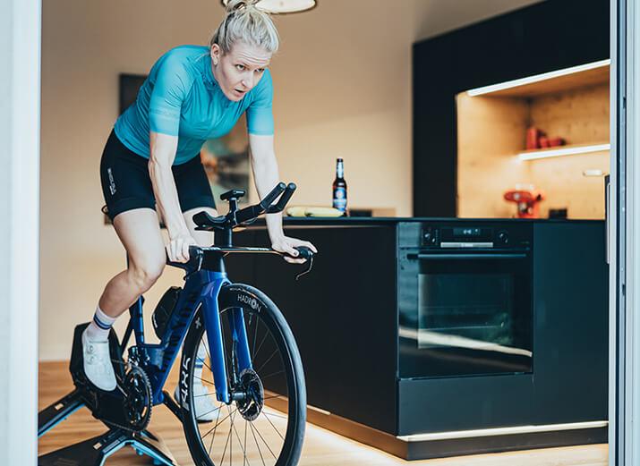 Eine Radsportlerin trainiert auf einem Rollentrainer mit Direktantrieb.