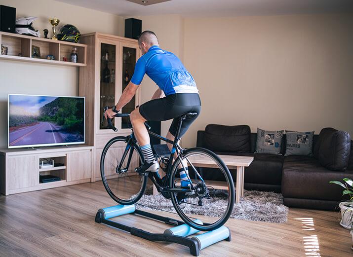 Ein Radsportler nutzt nutzt eine freie Rolle im Wohnzimmer.