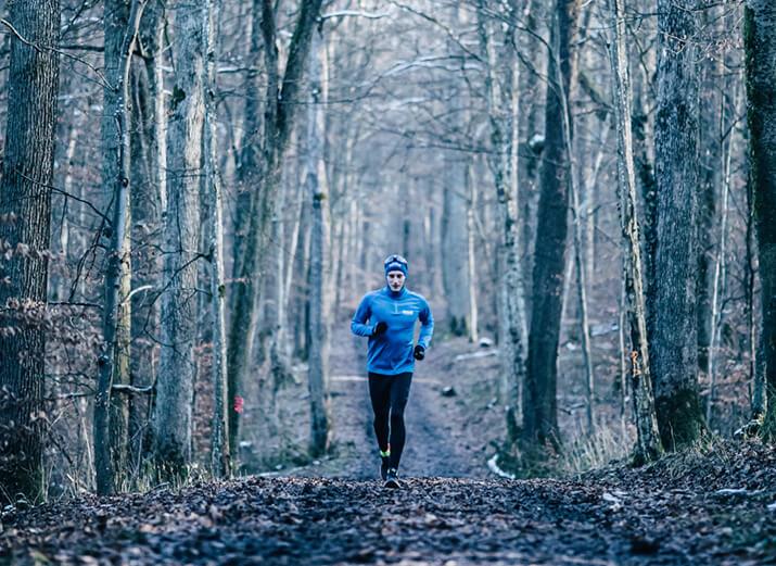 Ein Mann läuft im Winter bei Kälte im Wald.
