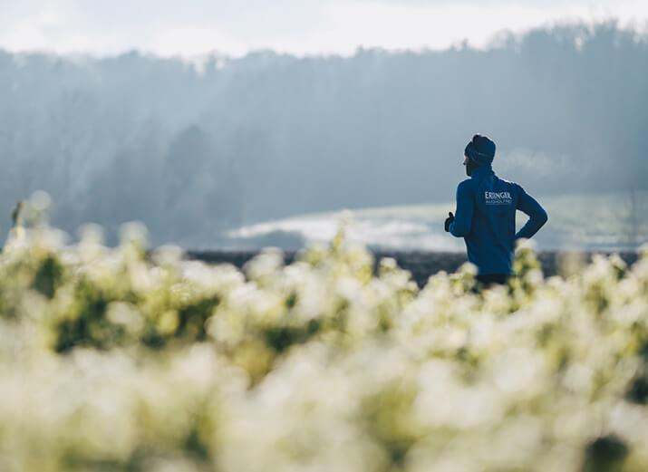 Ein Mann läuft im Winter bei sonnigem Wetter