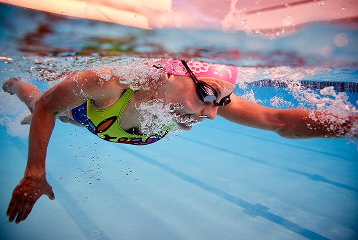 Eine Schwimmerin beim Kraulschwimmen im Wasserbecken.