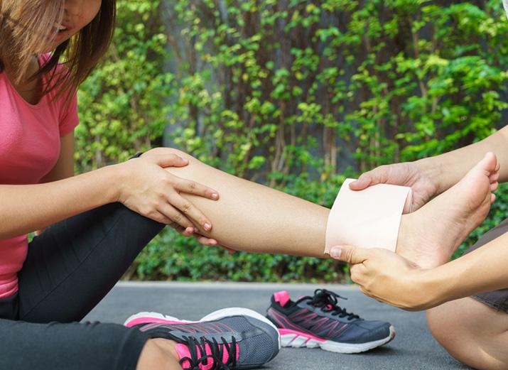 Eine Joggerin sitzt auf dem Boden. Ihr Knöchel wird von einer weiteren Person bandagiert.