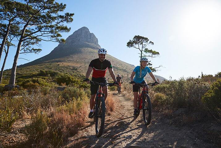 Drei Personen fahren glücklich mit ihrem Rennrad den Weg entlang, im Hintergrund ist ein Berg zu sehen.