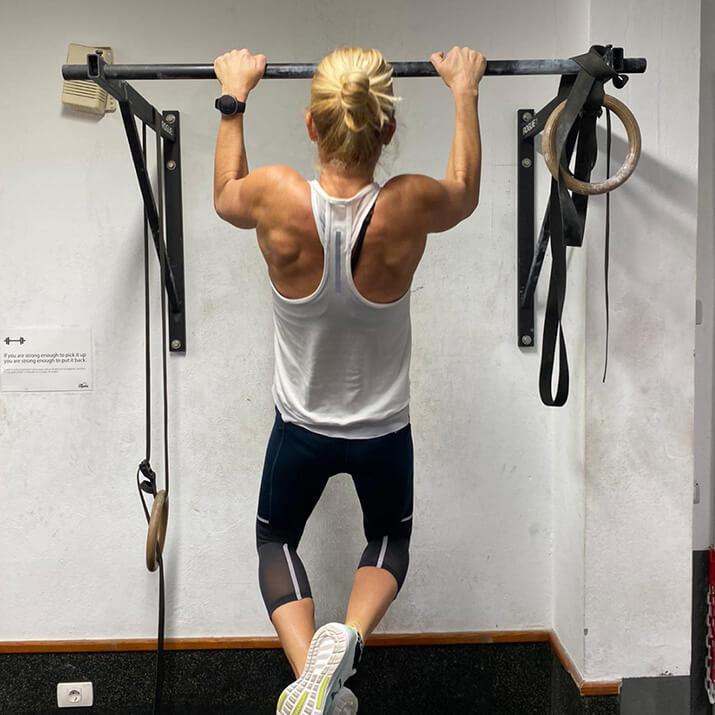 Eine Sportlerin zieht sich mit einem Klimmzug nach oben.