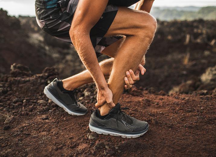 Jogger kniet und hält vor Schmerzen Achillessehne.