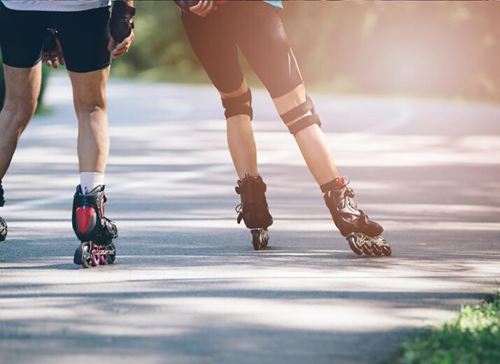 Zwei Skater fahren im Park Inliner, sie tragen Schutzausrüstung.
