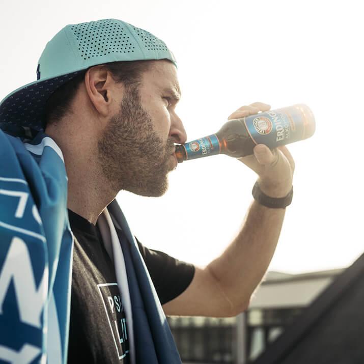 Ein Sportler belohnt sich mit einem Schluck aus einer Flasche.