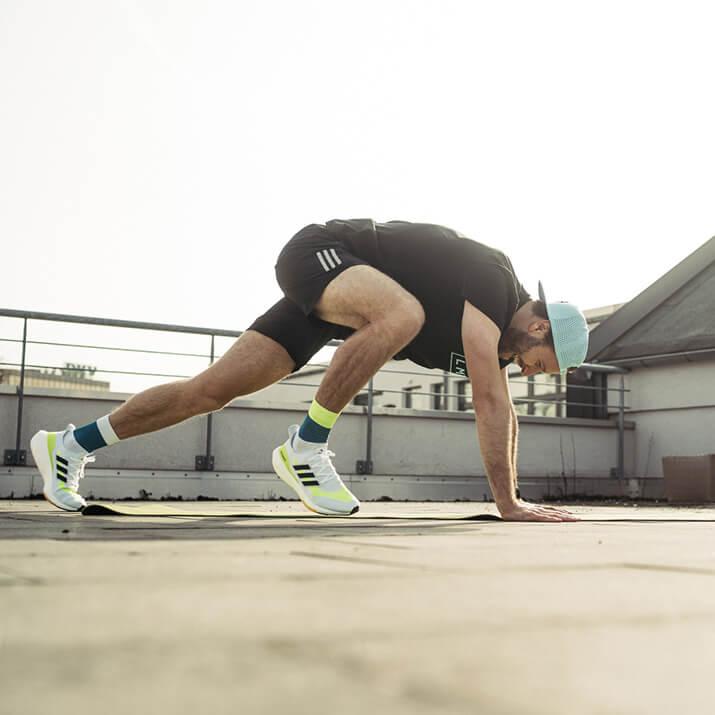 Ein Sportler macht Climbers auf einer Fitnessmatte.