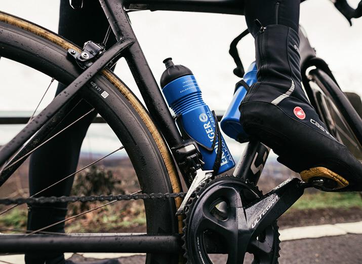 Ein Radfahrer auf dem Rad zeigt seine Überziehschuhe.