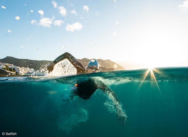 Ein Schwimmer mit Neoprenanzug im Freiwasser
