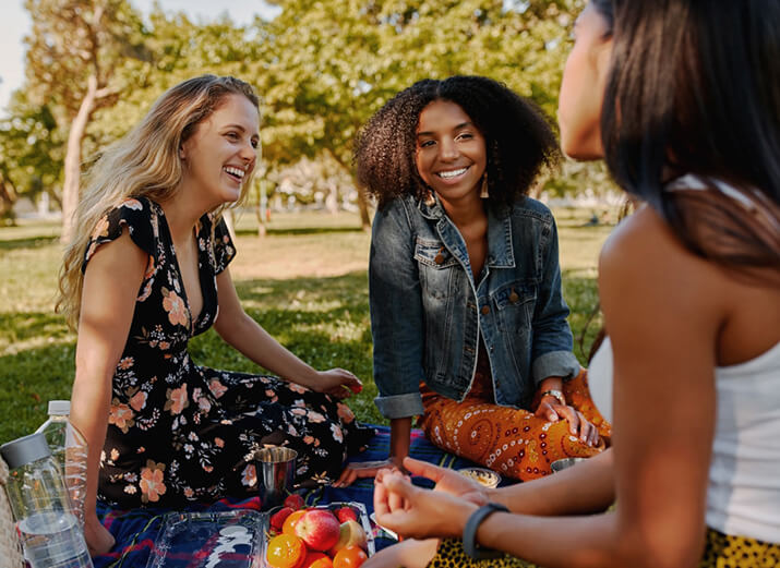 Drei Freundinnen picknicken und unterhalten sich.