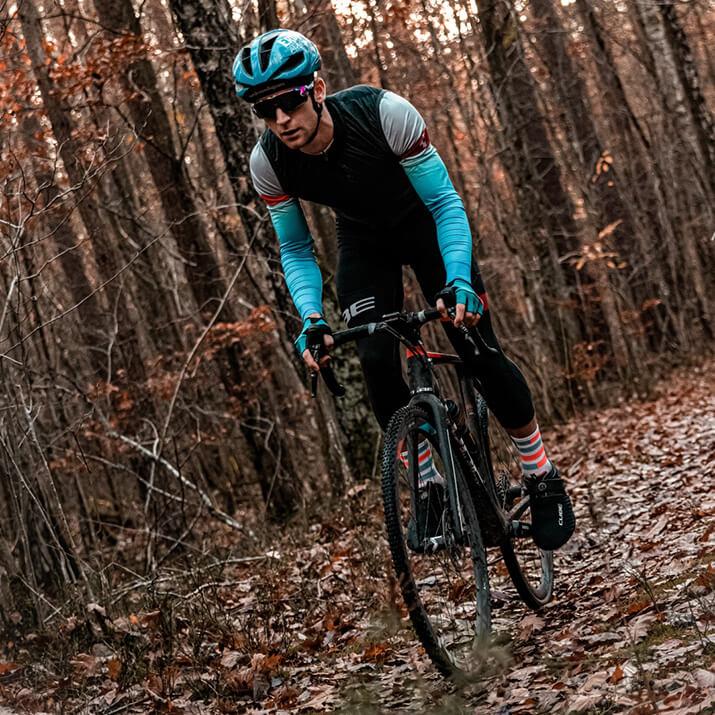 Ein Radsportler fährt mit einem Gravelbike im Wald.