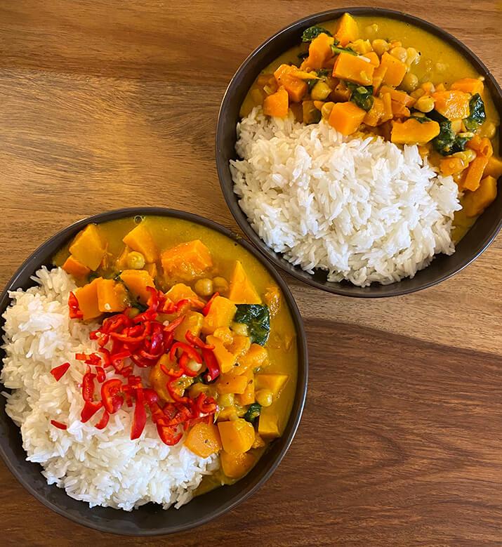 In zwei Schalen befinden sich Reis und ein Curry aus Kürbis und Süßkartoffeln.