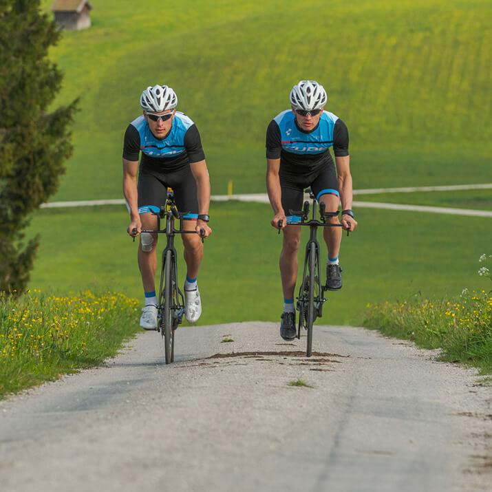 Zwei Radsportler gehen an einer Steigung aus dem Sattel.