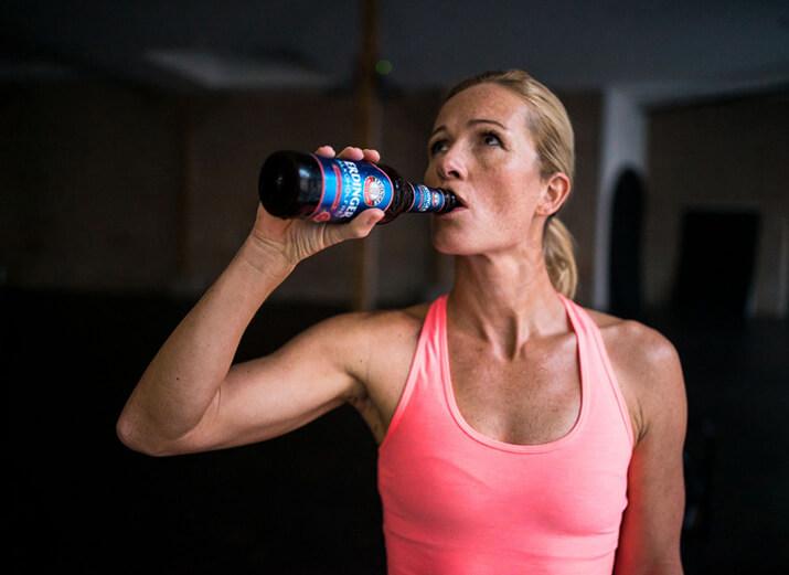 Eine Sportlerin trinkt ein alkoholfreies Bier aus einer Flasche.