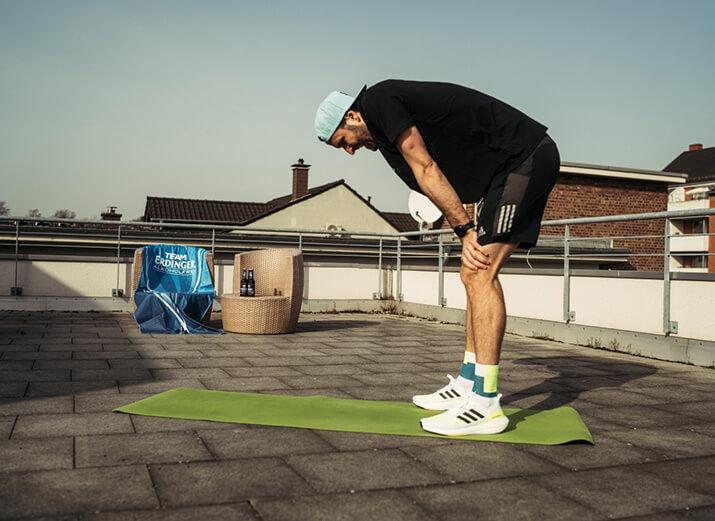 Ein Sportler pausiert sein Training, wegen eines Muskelkrampfes.