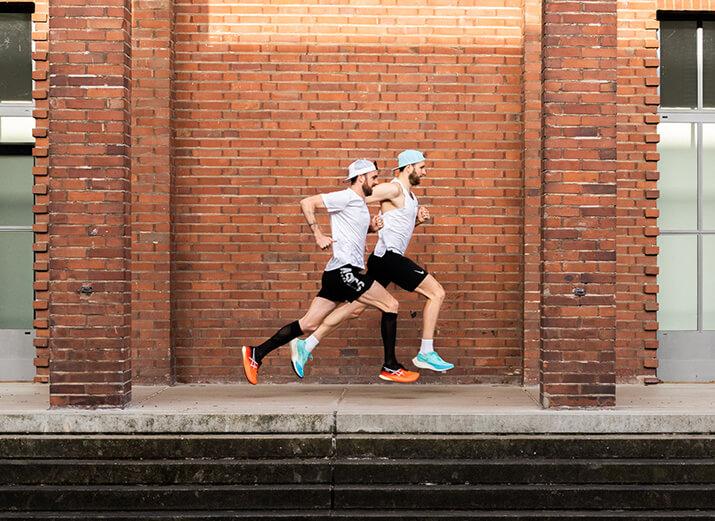 Zwei Läufer laufen vor einer roten Fassade.