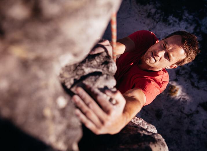 Ein Kletterer greift nach einem Felsvorsprung.