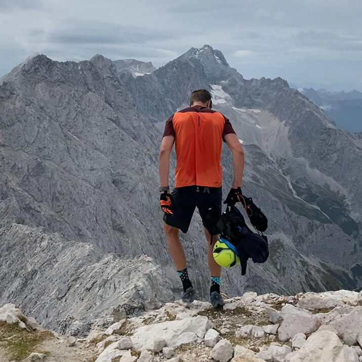 Ein Wanderer steht vor einem Bergpanorama.