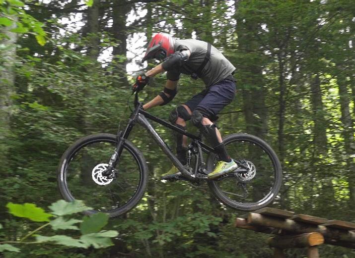 Ein Mountainbiker setzt zu einem Sprung an.
