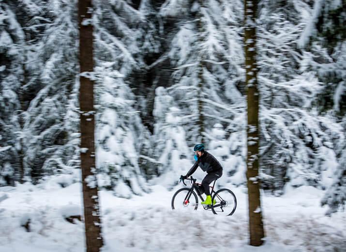 Ein Radfahrer fährt im Wald, im Hintergrund liegt Schnee.