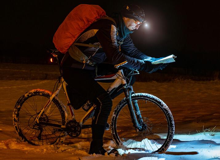 Ein Radfahrer studiert im Winter eine Karte mit einer Helmlampe.