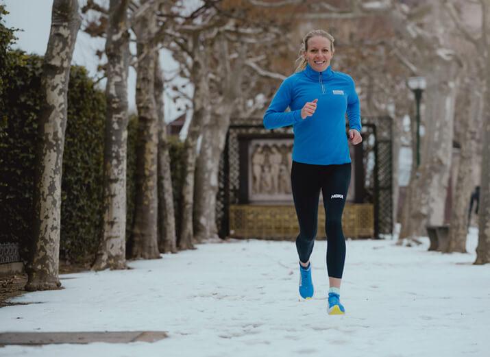 Lächelnde Frau joggt draußen auf einem verschneiten Weg.