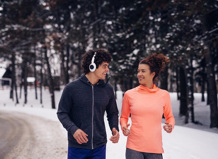 Eine Frau und ein Mann in Sportklamotten joggen langsam auf einem verschneiten Pfad.