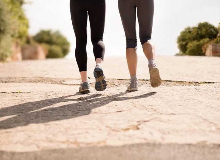Zwei Menschen in Sportklamotten laufen bergauf eine Straße hoch.