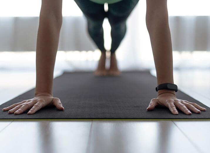 Eine Frau stützt sich mit Armen und Beinen auf einer Sportmatte ab. Ihre Arme und Hände befinden sich im Vordergrund. Die Beine sind unscharf im Hintergrund zu erkennen.