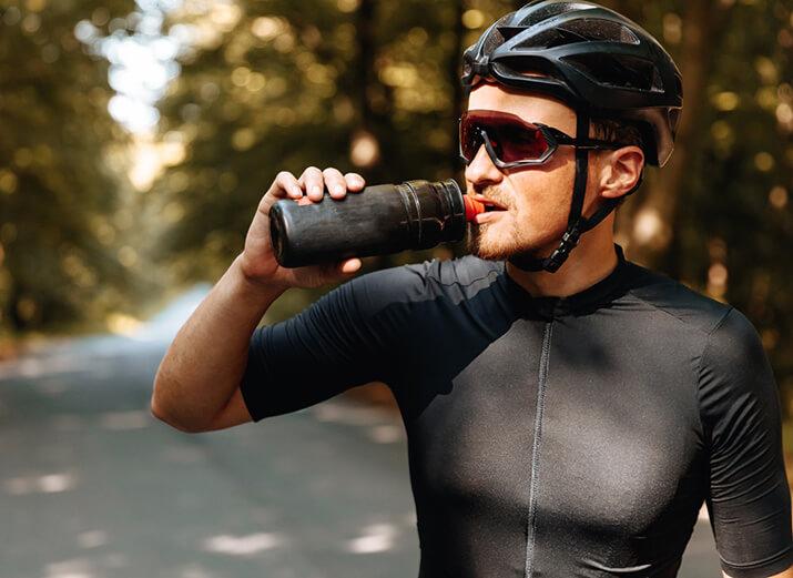 Ein Radsportler legt eine Pause ein, um einen Schluck zu trinken.