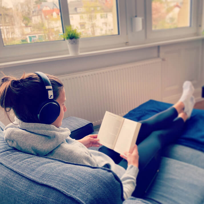 Eine Frau sitzt auf dem Sofa und regeneriert beim Lesen eines Buches.