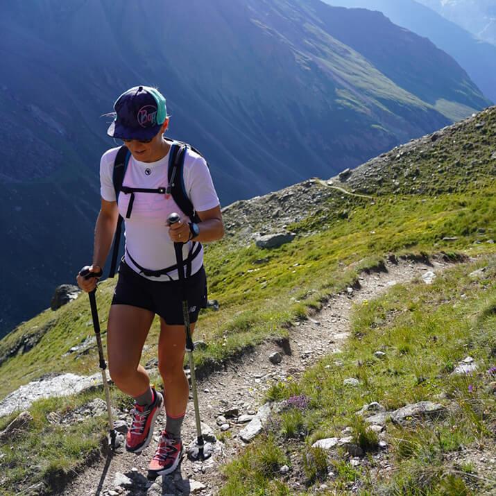 Eine Frau wandert mit Walking-Sticks durch eine Berglandschaft.