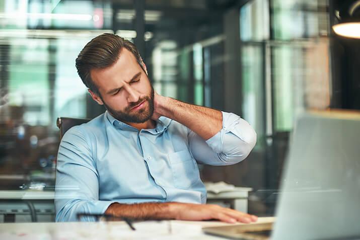 Mann reckt sich beim Arbeiten am Laptop im Sitzen.